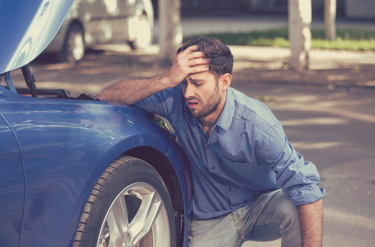 man frustrated leaning on car